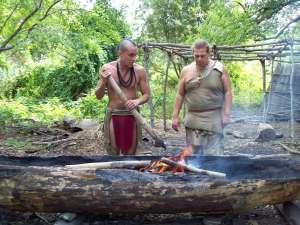 Two native men burning a log to be made into a canoe.